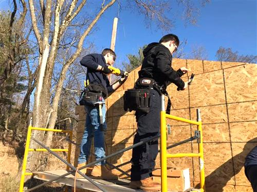 Carpentry students on scaffolding building a house