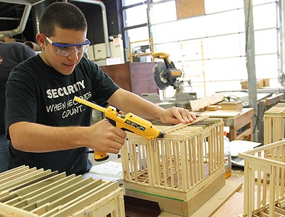 Carpentry student with drill working on a wooden construction model