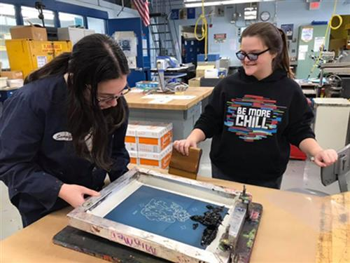 Two Graphic Communications students working on silk screen project