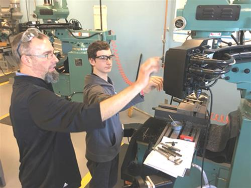 MEAM instructor working with student operating equipment
