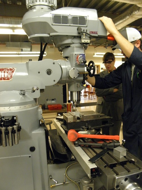 Two MEAM students operating equipment in class