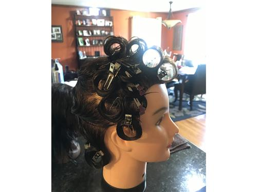 A paperclip and bobby pin are used to secure pin curls & rollers during a virtual Cosmetology class