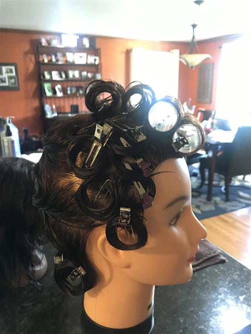 A paperclip and bobby pin are used to secure pin curls and rollers for a virtual Cosmetology class