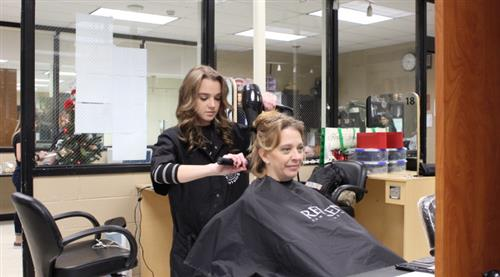 SCVTHS Cosmetology student performs a hair treatment at the school's annual Holiday Cut-A-Thon