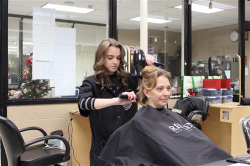 Cosmetology student working on donor during Cut-A-Thon holiday fundraiser