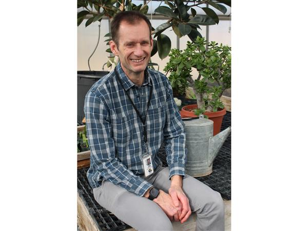 Erik Fargo, Educator of the Year at SCVTHS, smiling, seated with several plants surrounding him